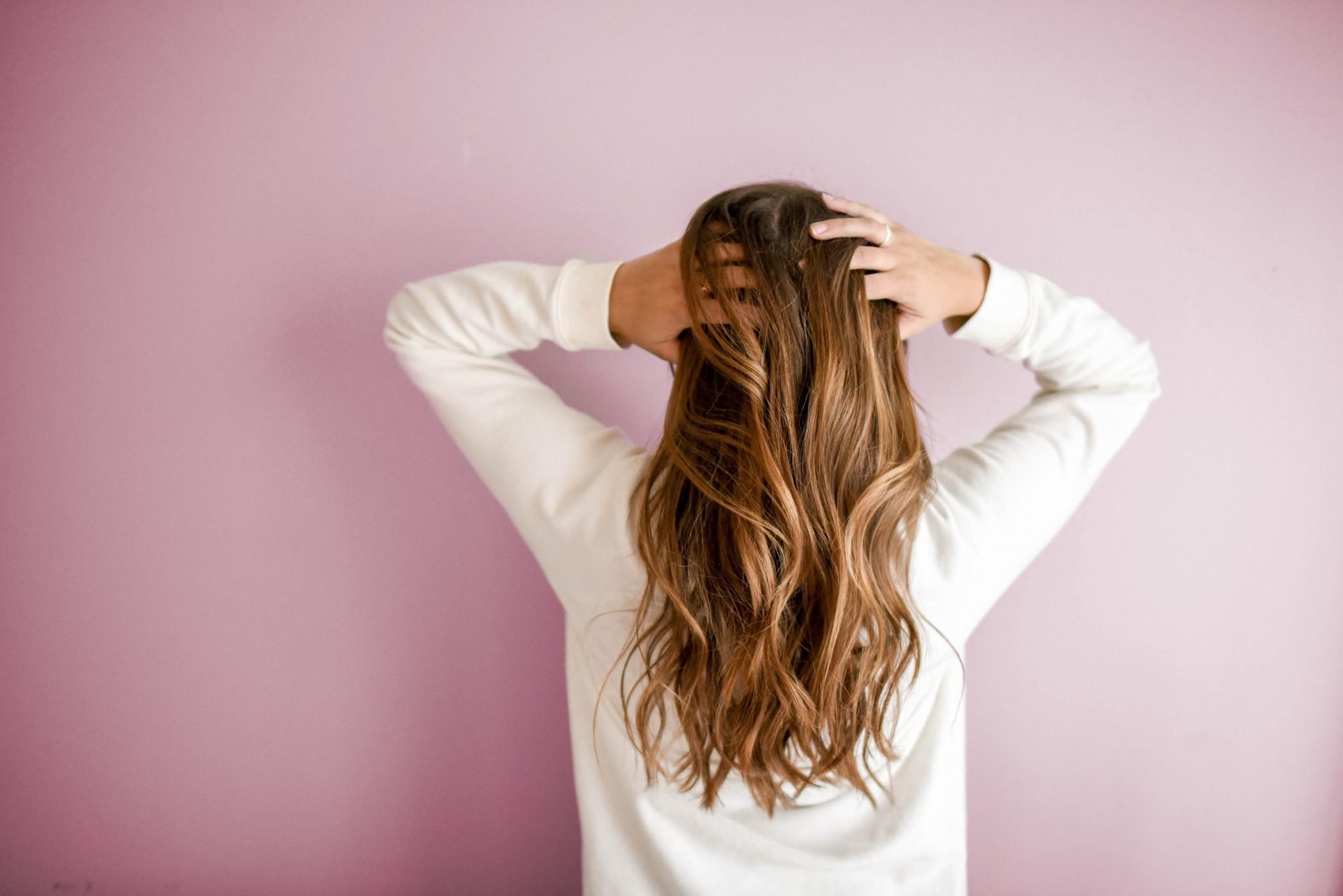 Frau mit langen Haaren von hinten hält ihr Kopf