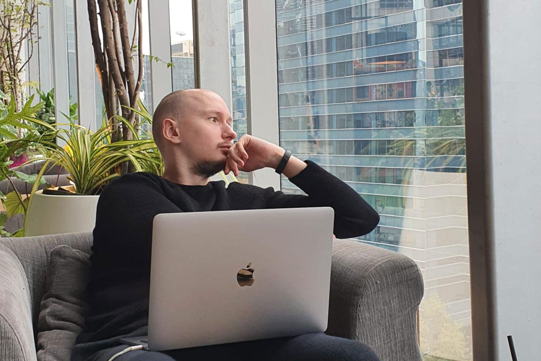 Simon schaut aus dem Fenster mit dem Mac Book auf dem Schoss